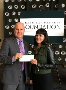 Pat Heier, from The Women's Community Board, and Jane Graham Jennings receive a grant check from The Green Bay Packers Foundation